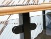 Detaljbild på glasräcke lackat i svart, med träöverliggare och rundade klämfästen